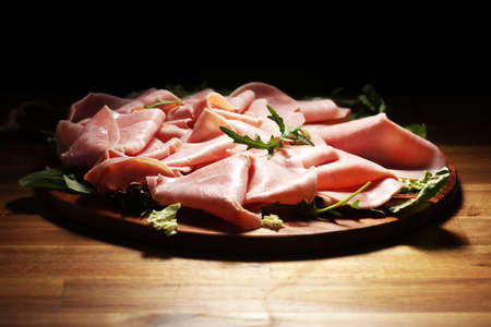 Sliced ham on wooden background. Fresh prosciutto. Pork ham sliced on board