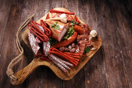 Vielzahl von Fleischprodukten einschließlich Schinken und Würstchen. Essenstablett mit leckerer Salami, Schinkenscheiben, Wurst und Salat