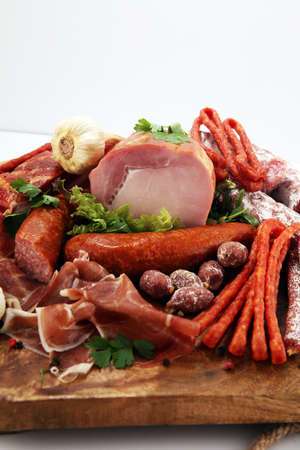 Variety of meat products including ham and sausages. Food tray with delicious salami, pieces of sliced ham, sausage and salad