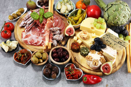 Italian antipasti wine snacks set. Cheese variety, Mediterranean olives, crudo, Prosciutto di Parma, salami and wine in glasses over wooden grunge background Фото со стока