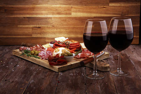 Cutting board with prosciutto, salami, coppa, cheese,bread sticks and olives on dark wooden background Reklamní fotografie