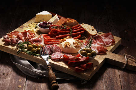 Cutting board with prosciutto, salami, coppa, cheese,bread sticks and olives on dark wooden background