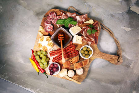 Cutting board with prosciutto, salami, coppa, cheese,bread sticks and olives on dark stone background