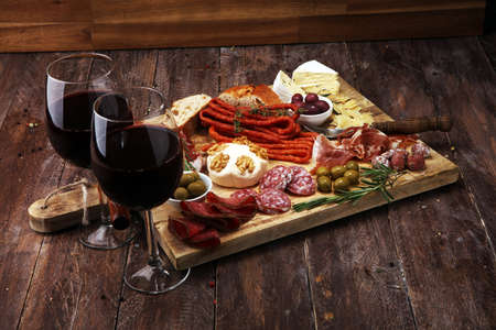 Cutting board with prosciutto, salami, coppa, cheese,bread sticks and olives on dark wooden background Imagens