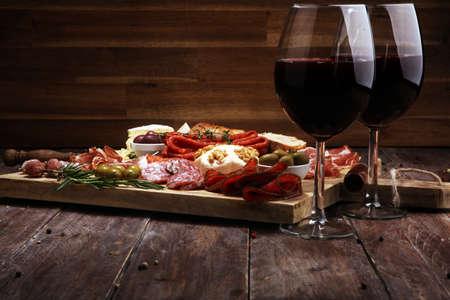Schneidebrett mit Schinken, Salami, Coppa, Käse, Brotstangen und Oliven auf dunklem Holzhintergrund Standard-Bild