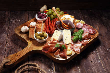 Cutting board with prosciutto, salami, coppa, cheese,bread sticks and olives on dark wooden background Фото со стока