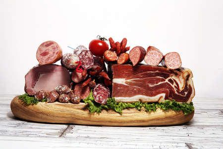 cold meat assortment with delicious salami and herbs. Variety of meat products including proscuitto, jamon  and sausages on wood