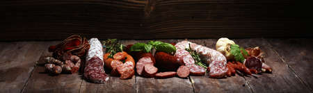 cold meat assortment with delicious salami and herbs. Variety of meat products including coppa and sausages on wood Stock Photo