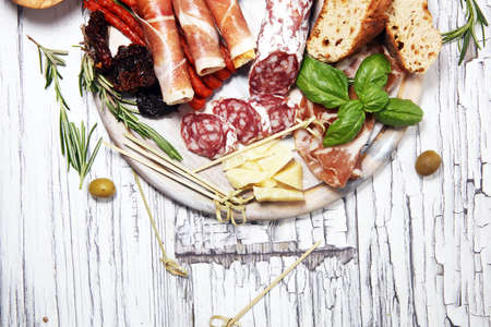 antipasto various appetizer. Cutting board with prosciutto, salami, coppa, cheese,bread sticks and olives on white wooden