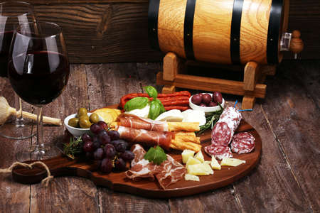 antipasto various appetizer. Cutting board with prosciutto, salami, coppa, cheese, bread sticks and olives on dark wooden Фото со стока