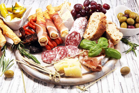 antipasto various appetizer. Cutting board with prosciutto, salami, coppa, cheese, bread sticks and olives on white wooden Archivio Fotografico