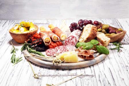 antipasto varios aperitivos. Tabla de cortar con jamón, salami, coppa, queso, palitos de pan y aceitunas en madera blanca Foto de archivo