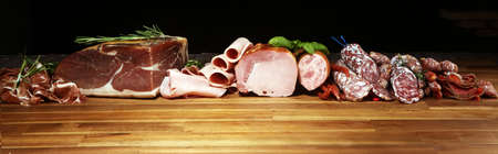cold meat assortment with delicious salami and herbs . Variety of meat products including coppa and sausages on wood