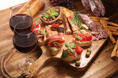 antipasto various appetizer. Cutting board with prosciutto, salami, coppa, cheese,bread sticks and olives on dark wooden