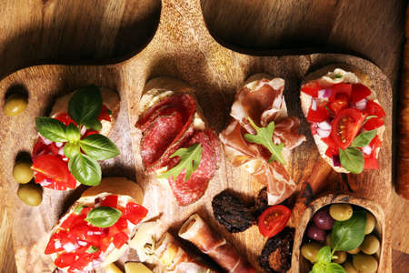 Traditional italian antipasto bruschetta appetizer with cherry tomatoes, cream cheese, basil leaves and balsamic vinegar on cutting board with prosciutto, salami, cheese,bread and olives Фото со стока