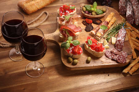 Traditional italian antipasto bruschetta appetizer with cherry tomatoes, cream cheese, basil leaves and balsamic vinegar on cutting board with prosciutto, salami, cheese,bread and olives Archivio Fotografico