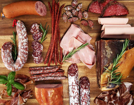 cold meat assortment with delicious salami and herbs . Variety of meat products including coppa and sausages on wood flat lay Фото со стока
