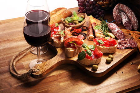 Traditional italian antipasto bruschetta appetizer with cherry tomatoes, cream cheese, basil leaves and balsamic vinegar on cutting board with prosciutto, salami, cheese,bread and olives Banque d'images