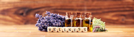 lavender oil in a glass bottle on a background of fresh flowers and Wellness sign with wooden cubes