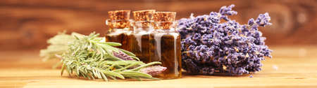 lavender oil in a glass bottle on a background of fresh flowers