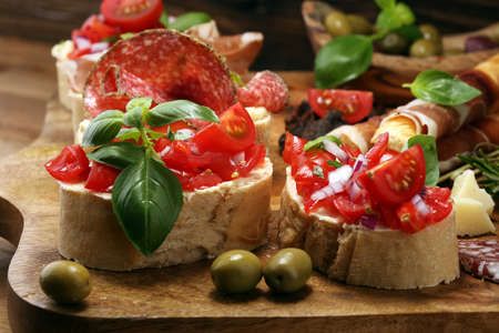Traditional italian antipasto bruschetta appetizer with cherry tomatoes, cream cheese, basil leaves and balsamic vinegar on cutting board with prosciutto, salami, cheese,bread and olives