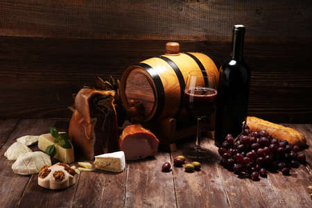Antipasto and red wine. Still life in a rustic style. Grapes on a wooden table with a bottle of wine and exquisite meat and cheese. Reklamní fotografie