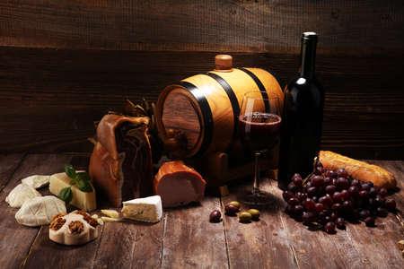 Antipasto y vino tinto. Bodegón de estilo rústico. Uvas en una mesa de madera con una botella de vino y exquisitas carnes y quesos. Foto de archivo
