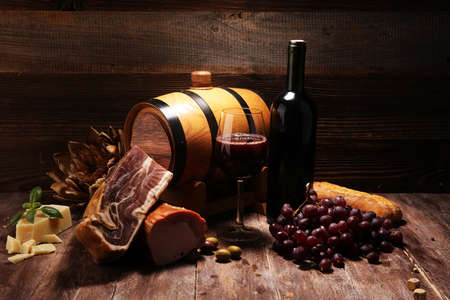 Antipasto and red wine. Still life in a rustic style. Grapes on a wooden table with a bottle of wine and exquisite meat and cheese.