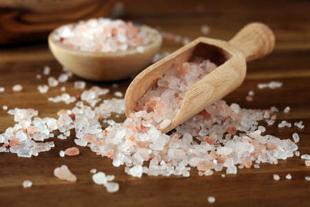 Natuaral cosmetics with pink himalayan spa salt. Sea bath salt for spa relaxation on wooden background