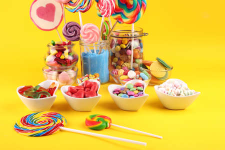 candies with jelly and sugar. colorful array of different childs sweets and treats on yellow