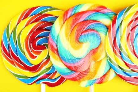 Lutschbonbons mit Zucker. Bunte Auswahl an Lutscher-Süßigkeiten und Leckereien für Kinder auf Gelb