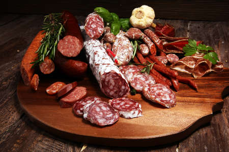 Food tray with delicious salami and herbs . Variety of meat products including coppa and sausages. cold meat