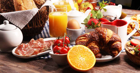 Huge healthy breakfast on table with coffee, orange juice, fruits, waffles and croissants. Cereals and balanced died. Good morning concept. Stock Photo