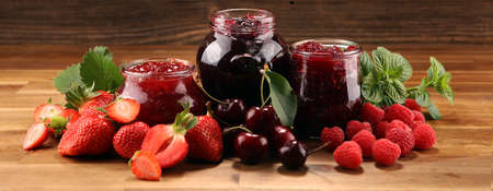 assortment of jams, seasonal berries, cherries, mint and fruits with strawberry Banco de Imagens