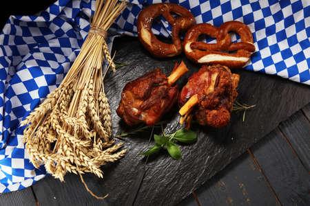 Traditional German cuisine, Schweinshaxe roasted ham hock. pretzels Bavarian specialties. Oktoberfest background with pork  knuckle Stock Photo