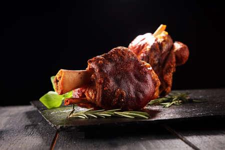 Geräucherter Schinken mit Kräutern und Gewürzen. Gebratene Schweinshaxe. Schinken und Speck sind im Westen beliebte Lebensmittel. Deutsche Schweinshaxe oder Haxe