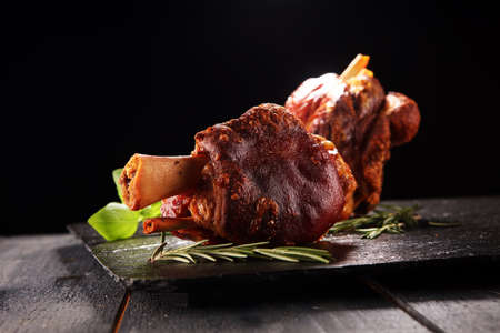 Smoked ham hock with herbs and spices. Roasted pork knuckle. Ham and bacon are popular foods in the west. German Schweinshaxe or Haxe Stock Photo