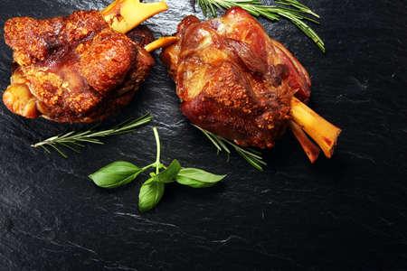 Geräucherter Schinken mit Kräutern und Gewürzen. Gebratene Schweinshaxe. Schinken und Speck sind im Westen beliebte Lebensmittel. Deutsche Schweinshaxe oder Haxe Standard-Bild