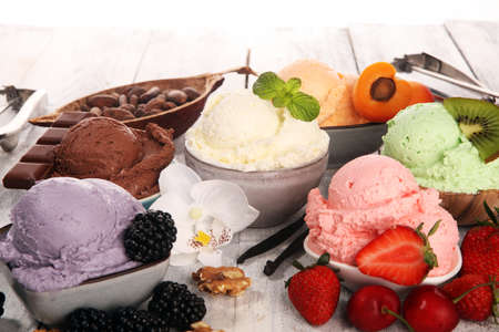 Set of ice cream scoops of different colors and flavors with berries, nuts and fruits decoration on white background