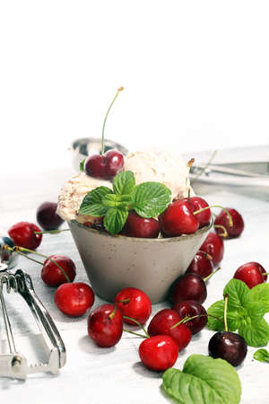 Cherry ice cream scoop with fresh cherries on a rustic background Stock Photo