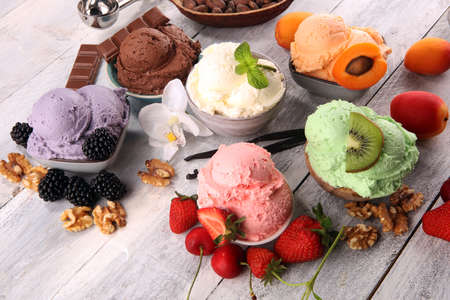 Set of ice cream scoops of different colors and flavors with berries, nuts and fruits decoration on white background Imagens