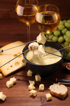 Gourmet Swiss fondue dinner on a winter evening with assorted cheeses on a board alongside a heated pot of cheese fondue with forks dipping bread