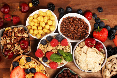 Cereal. Bowls of various cereals, fruits and milk for breakfast. Muesli with variety of kids cereals. Stock Photo