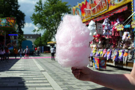 amusement park eating cotton candy. enjoying a day at amusement park with fresh white cotton candy in hand Stock Photo