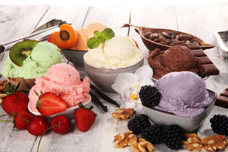Set of ice cream scoops of different colors and flavours with berries, nuts and fruits decoration on white background