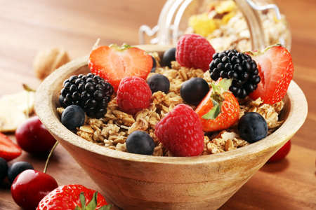 Bowl of granola cereals, fruits and milk for breakfast. Oat flakes or Granola Muesli Stock Photo
