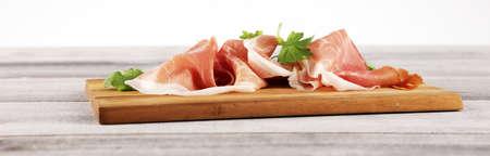 Italian prosciutto crudo or jamon with fresh parsley. Raw ham.