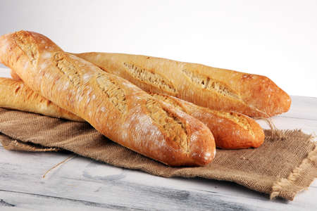 Assortment of baked bread and bread rolls on wooden table background. Bakery poster concept