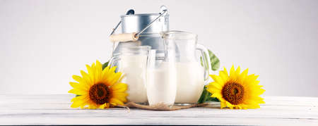 A jug of milk and glass of milk on a wooden table and sunflower 写真素材