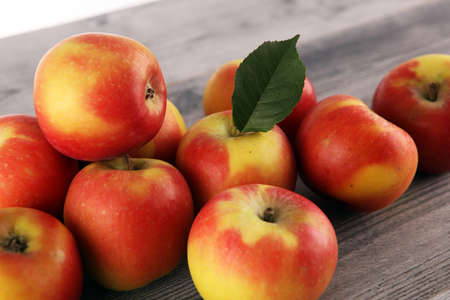 Ripe red apples with leaves on light wooden background